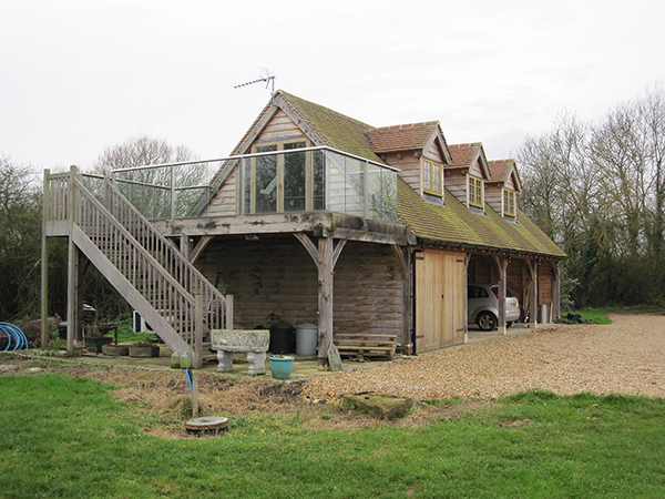 Oak framed 4 bay garage with room above and balcony by Shires Oak Buildings