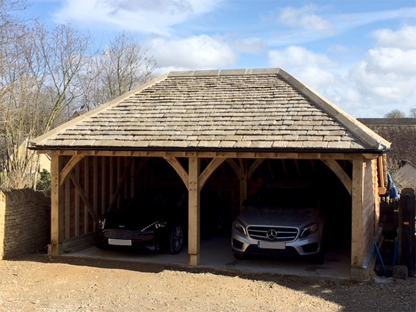 Oak framed 2 bay garage with hipped roof by Shires Oak Buildings