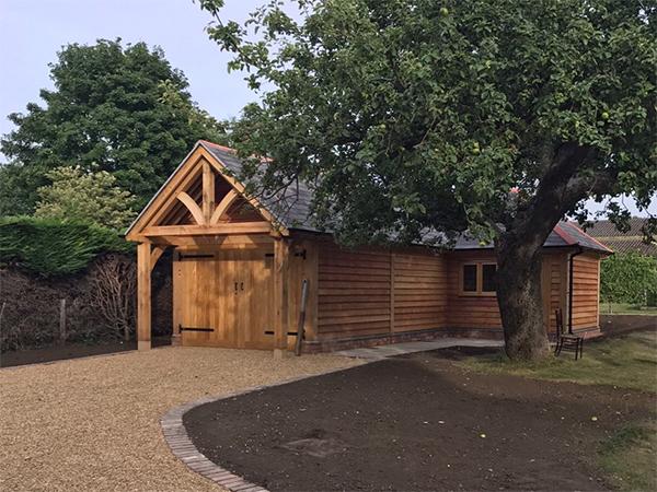 Oak framed L-shaped garage & workshop by Shires Oak Buildings