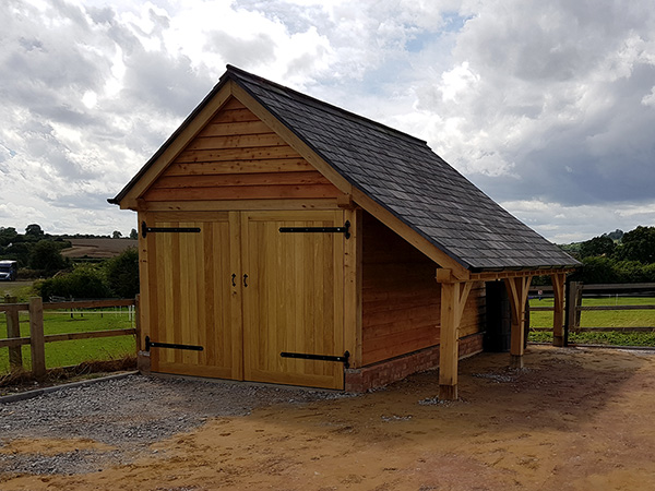 Oak framed 1 bay garage with logstore by Shires Oak Buildings