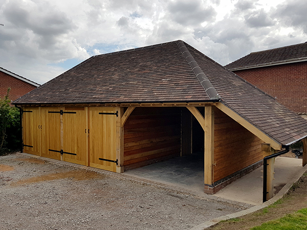 Oak framed 3 bay garage with hipped roof and logstore by Shires Oak Buildings
