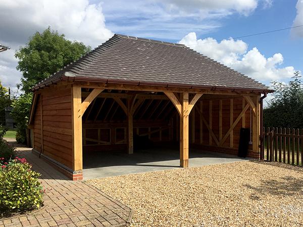 Oak framed 2 bay hipped roof garage by Shires Oak Buildings