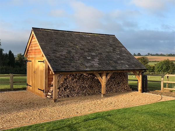 Oak framed garage with logstore by Shires Oak Buildings