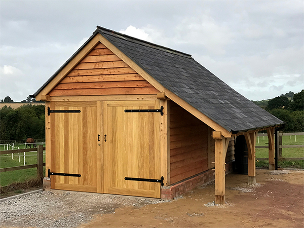 Oak framed single garage with logstore by Shires Oak Buildings