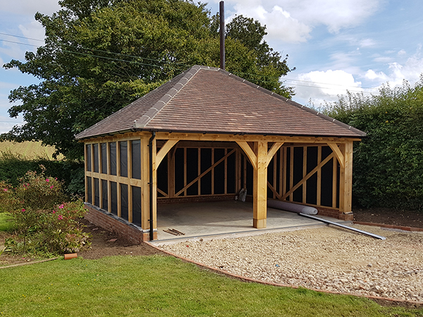 Oak framed 2 bay garage with hipped roof and rendered side panels by Shires Oak Buildings