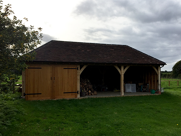 Oak framed 3 Bay Garage with hipped roof and 1 enclosed bay by Shires Oak Buildings