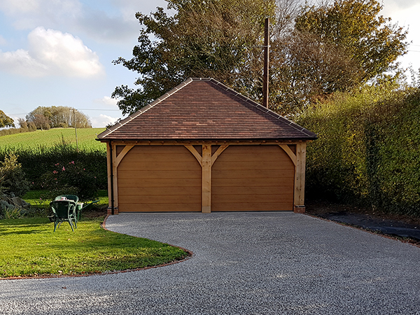 Oak framed 2 bay garage by Shires Oak Buildings, with hipped roof, rendered side panels & automated sectional doors