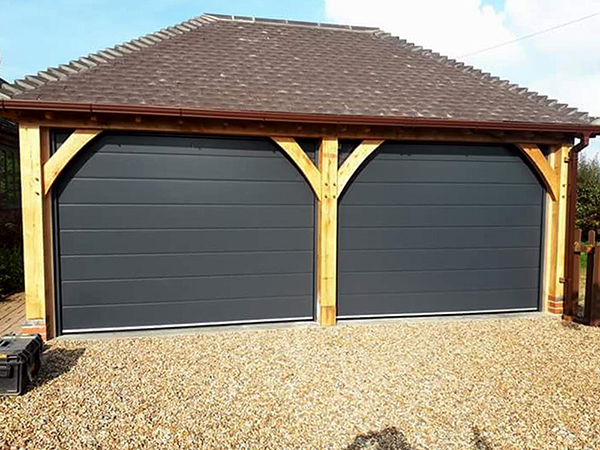 Oak framed 2 bay garage with hipped roof and automated doors by Shires Oak Buildings