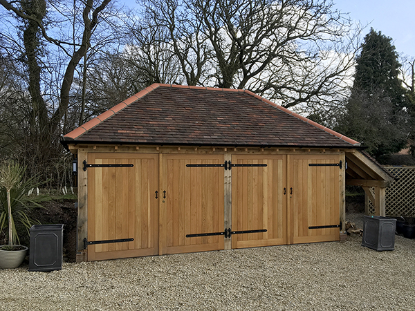 Oak framed 2 bay garage with hipped roof & logstore by Shires Oak Buildings