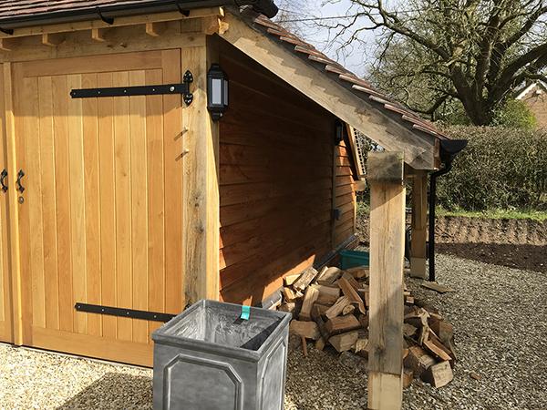 Oak framed 2 bay garage with hipped roof, logstore & oak doors by Shires Oak Buildings