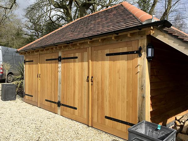 Oak framed 2 bay garage with hipped roof & oak doors by Shires Oak Buildings