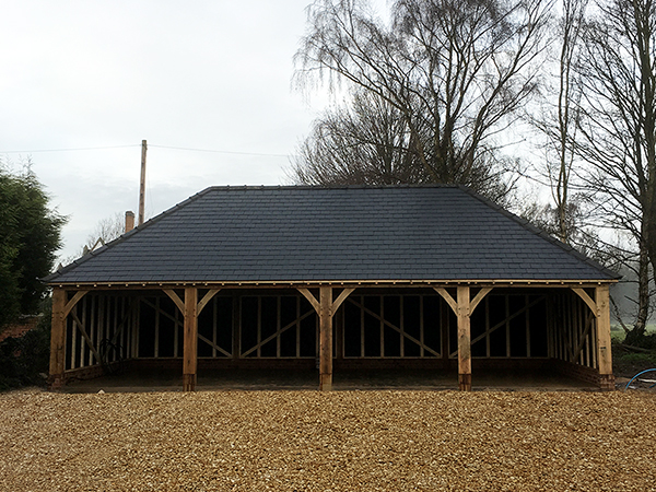 Oak framed 4 bay garage with hipped roof in new slate by Shires Oak Buildings