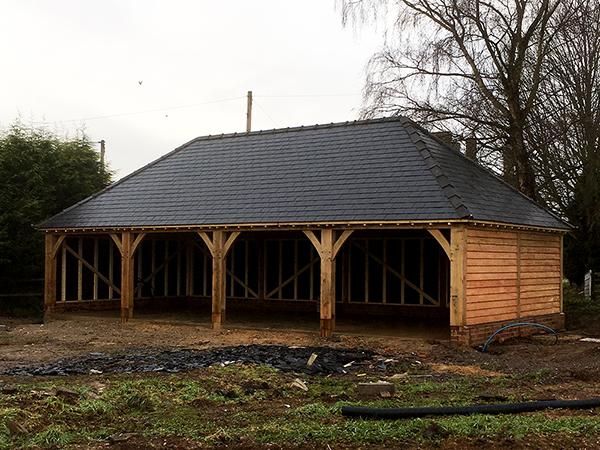 Oak framed 4 bay garage with hipped roof in slate by Shires Oak Buildings