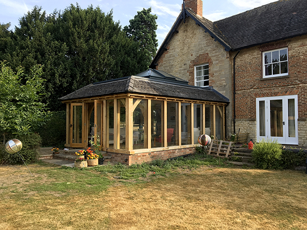 Oak framed orangery with hipped rooflight and mansard roof, by Shires Oak Buildings