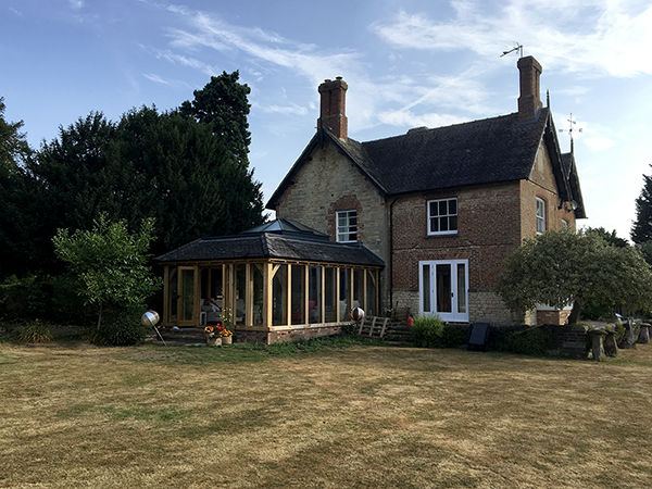 Oak framed orangery with hipped rooflight, French doors and mansard roof, by Shires Oak Buildings