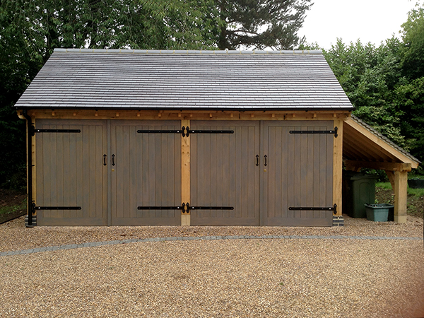 Oak framed 2 bay garage with logstore to right hand side by Shires Oak Buildings