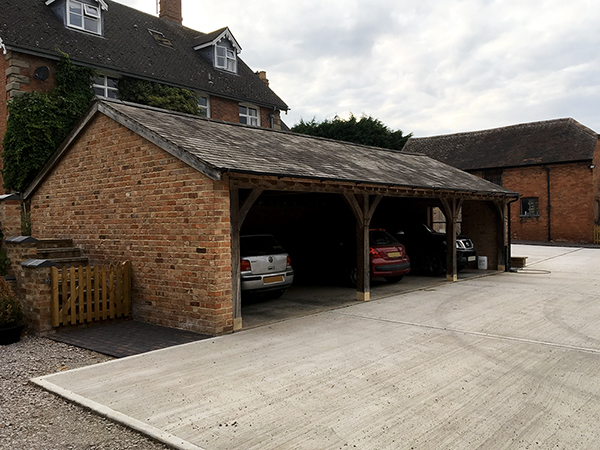 Oak framed 3 bay garage with brick gable end by Shires Oak Buildings