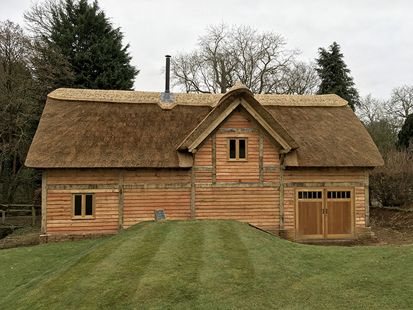 Oak framed mill building with thatched roof by Shires Oak Buildings