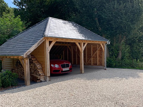 Oak framed 2 bay garage with hipped roof and logstore to left hand side, by Shires Oak Buildings