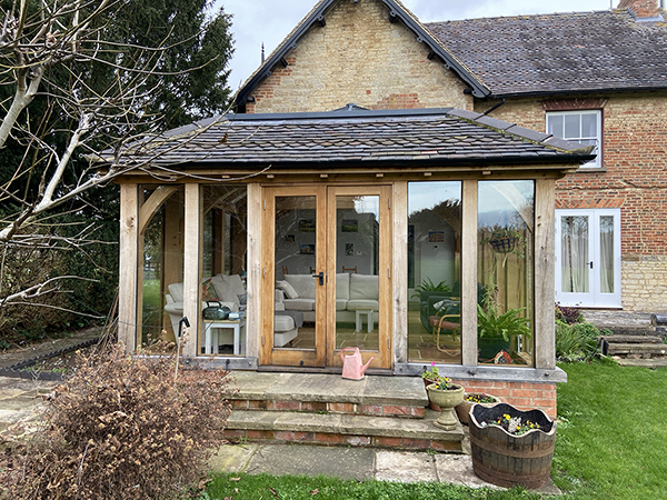 Oak framed orangery with mansard roof, front elevation and French doors, by Shires Oak Buildings